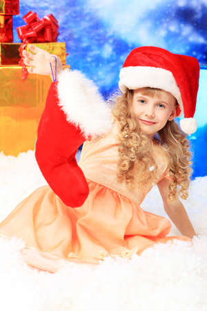 Christmas kid in Santa hat sitting in snowdrift. Stock Photo - 6174110
