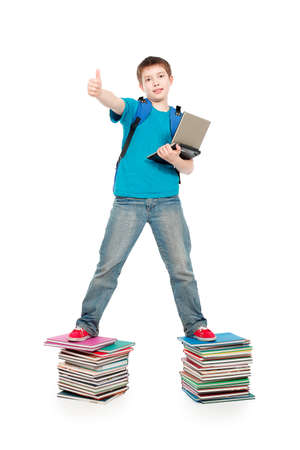 book boy: Portrait of a scoolboy standing on a stack of books.