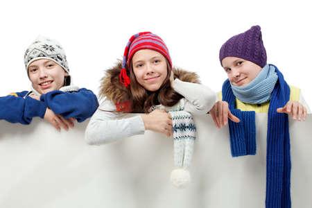 warm clothes: Gruppo di adolescenti in vestiti pesanti, guardando fuori bordo bianco. Archivio Fotografico