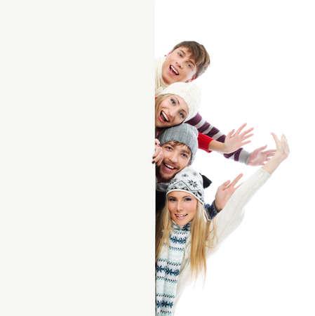 warm clothes: Gruppo di giovani in vestiti pesanti, guardando fuori bordo bianco. Archivio Fotografico