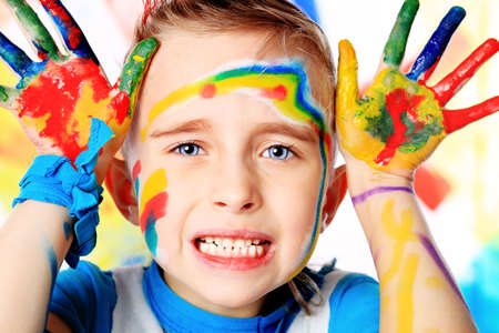 children painting: Portrait of a beautiful child enjoying his painting. Education. Stock Photo