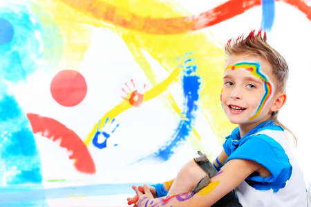 Retrato de un hermoso niño disfruta de su pintura. Educación. Foto de archivo