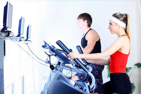 Couple of a sporty young people in the gym.  photo
