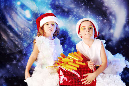 Beautiful little angelic children with a present at a stellar sky. photo