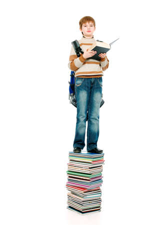 Portrait of a scoolboy standing on a stack of books. photo