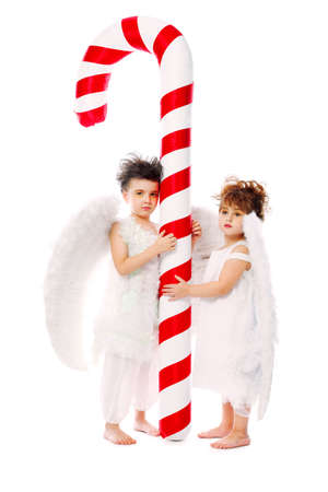 Beautiful little angels with a huge candy isolated over white background. photo