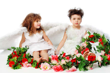 defenceless: Beautiful little angels holding flowes. Isolated over white background. Stock Photo