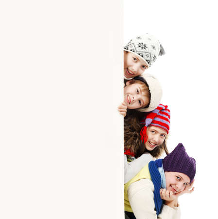 winter fashion: Group of teenagers in warm clothes looking out white board.