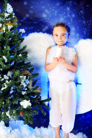 Beautiful little angelic child  with a candle at a christmas background. photo