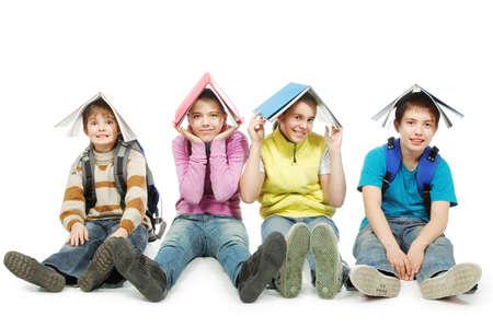 adolescentes estudiando: Tema educativo: Grupo de adolescentes sentados juntos y celebraci�n de libros sobre sus cabezas.