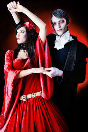 costume ball: Portrait of a beautiful dancing couple in medieval costumes with vampire style make-up. Shot in a studio.