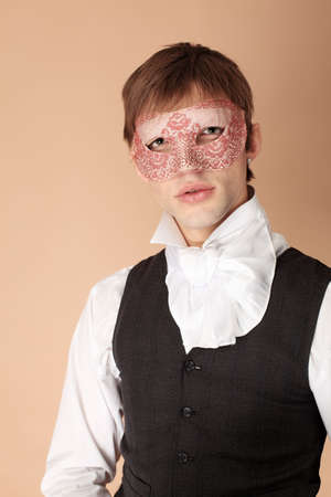 Portrait of a young gentlemen wearing dinner jacket and a mask. Shot in a studio. photo