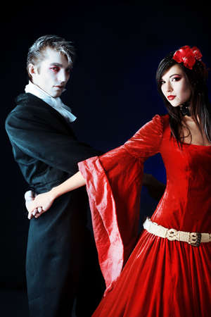 Portrait of a beautiful dancing couple in medieval costumes with vampire style make-up. Shot in a studio. Stock Photo - 6353090