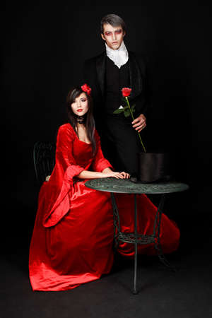 century: Portrait of a beautiful couple in medieval costumes with vampire style make-up. Shot in a studio. Stock Photo