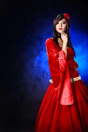 velvet dress: Portrait of a beautiful woman in medieval era dress. Shot in a studio. Stock Photo