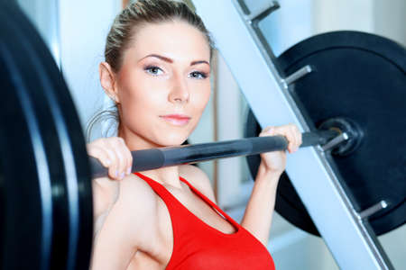 muscular build: Young sporty woman in the gym centre.