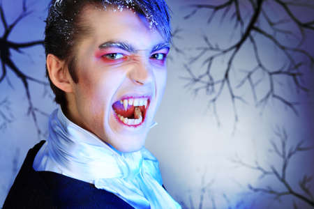 bared teeth: Portrait of a handsome young man with vampire style make-up. Shot in a studio. Stock Photo