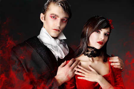 cosplay: Portrait of a beautiful couple in medieval costumes with vampire style make-up. Shot in a studio. Stock Photo
