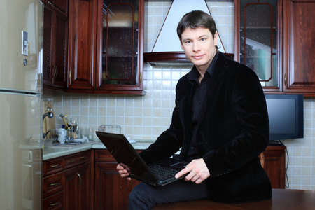 Handsome stylish man at home with a laptop photo