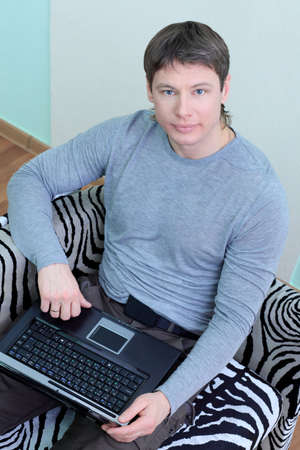 outwork: Handsome stylish man at home with a laptop