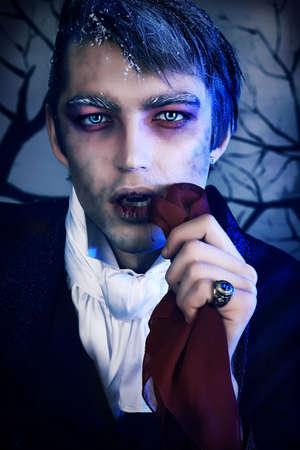 vampira sexy: Retrato de un joven apuesto con maquillaje de estilo de vampiro. Rodada en un estudio. Foto de archivo