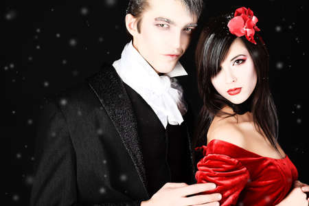 Portrait of a beautiful couple in medieval costumes with vampire style make-up. Shot in a studio. Stock Photo - 6437398