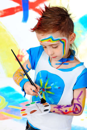 Portrait of a beautiful child enjoying his painting. Education. photo
