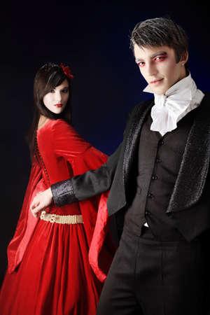 vampira sexy: Retrato de una hermosa pareja en trajes medievales con maquillaje de estilo de vampiro. Filmada en un estudio.