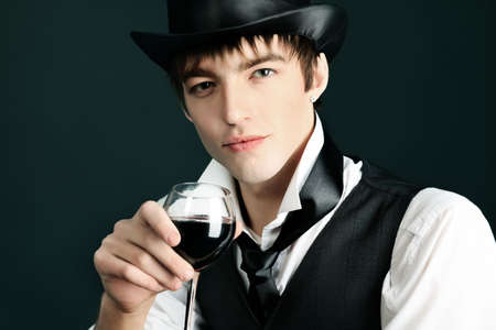 18th: Portrait of a young gentlemen wearing dinner jacket and black top hat. Shot in a studio.