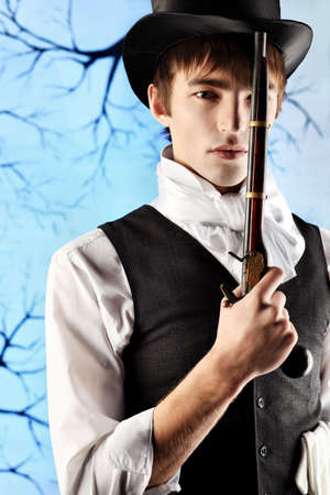 holiday movies: Portrait of a young gentlemen in a jacket and  top hat holding gun in his hand. Shot in a studio.