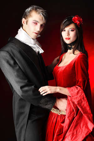 female vampire: Portrait of a beautiful couple in medieval costumes with vampire style make-up. Shot in a studio. Stock Photo