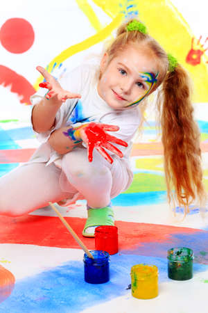 Portrait of a beautiful child enjoying her painting. Education. photo