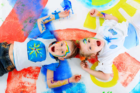 children painting: Two beautiful children enjoying their painting. Education.