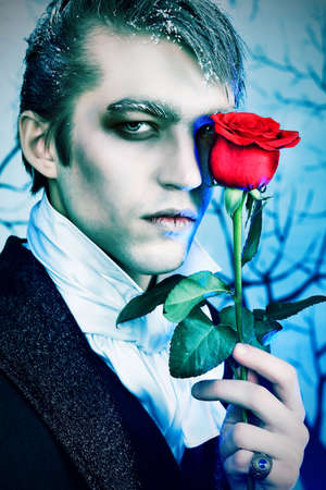 vampire: Portrait of a handsome young man with vampire style make-up. Shot in a studio. Stock Photo