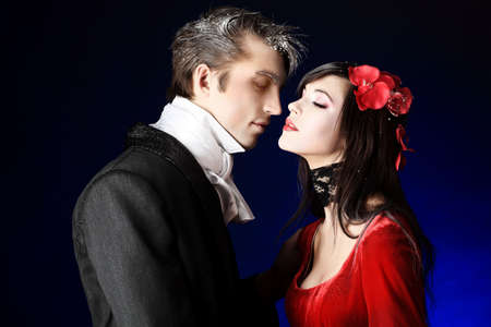 costume ball: Portrait of a beautiful couple in medieval costumes with vampire style make-up. Shot in a studio. Stock Photo
