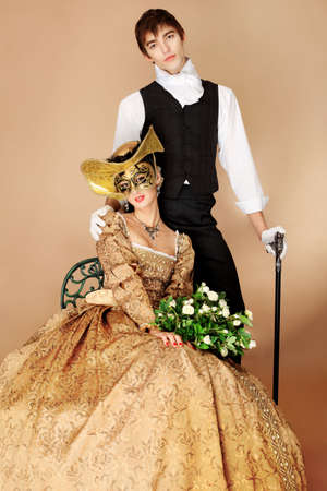 Portrait of a beautiful couple in medieval era costumes. Shot in a studio. photo