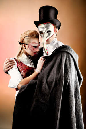 cloak: Portrait of the elegant young couple in masquerade costumes. Shot in a studio.