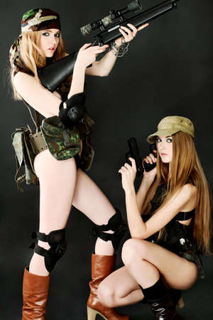 Two sexy women in military uniform posing against black background. photo