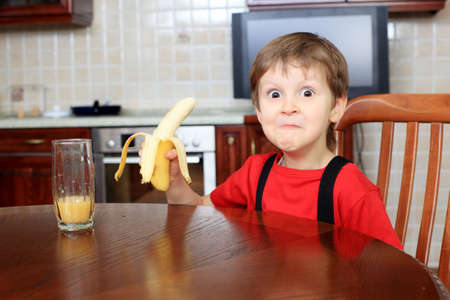 Little boy is eating a banana at home. Stock Photo - 11692188