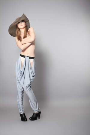 Shot of an attractive topless woman in jeans and big elegant hat. Stock Photo - 6560224