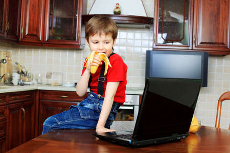 Little boy with his laptop at home. photo