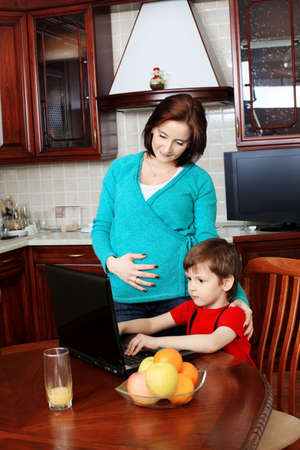 Happy pregnant woman with her son at home. photo