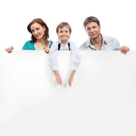 Portrait of a happy family holding a billboard. Isolated over white background. Stock Photo - 6595741