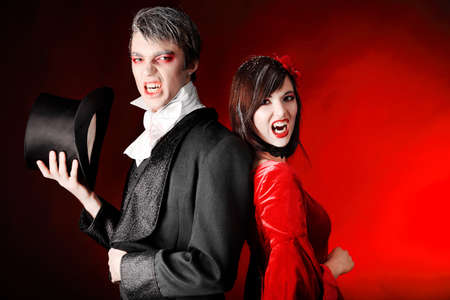bared teeth: Portrait of a beautiful couple in medieval costumes with vampire style make-up. Shot in a studio. Stock Photo