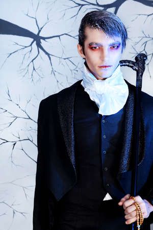 costume ball: Portrait of a handsome young man with vampire style make-up. Shot in a studio. Stock Photo