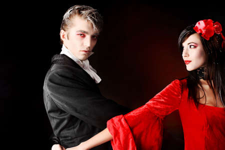 Portrait of a beautiful dancing couple in medieval costumes with vampire style make-up. Shot in a studio. photo