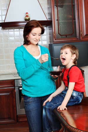 Happy pregnant woman with her son at home. Stock Photo - 11692113