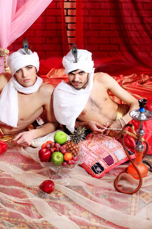 maharaja: Shot of two men in oriental costumes having a rest and smoking hookah. Stock Photo
