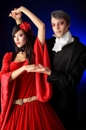 Portrait of a beautiful dancing couple in medieval costumes with vampire style make-up. Shot in a studio. Stock Photo - 6643628