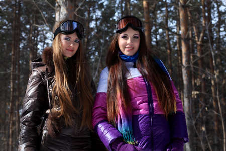Two pretty young women having a rest outdoor in winter. photo